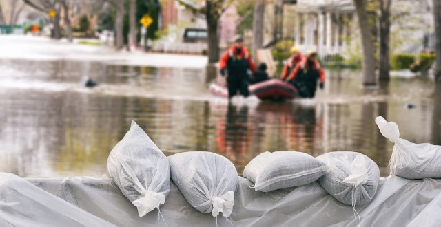 Flood Protection Sandbags with flooded homes in the background